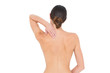 Rear view of a topless fit woman with shoulder pain