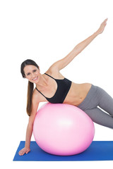 Portrait of a fit woman stretching on fitness ball