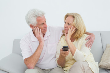 Relaxed senior couple watching television