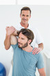 Male physiotherapist stretching a young man's arm