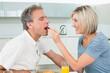 Loving woman feeding man in the kitchen
