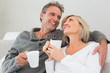 Relaxed happy couple with coffee cups in living room