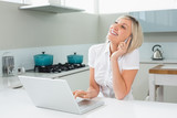 Cheerful woman using laptop while on call in kitchen