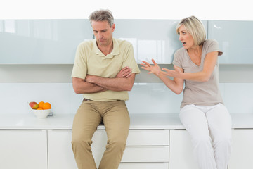 Man with arms crossed as woman argue in kitchen