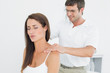 Male chiropractor massaging a young woman's shoulder