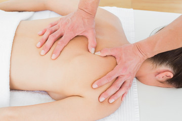 Close-up of male physiotherapist massaging woman's back