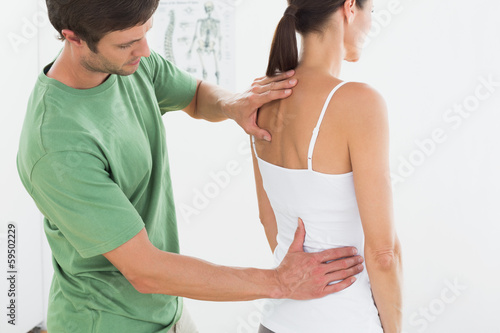 Male physiotherapist examining woman's back