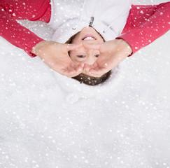Kind liegt im Winter im Schnee mit Herz