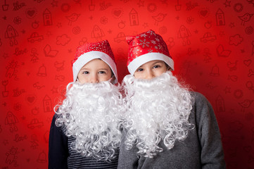 Young brothers funny portrait with xmas hat and beard against re