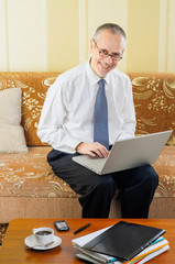 Friendly Senior Businessman with Computer