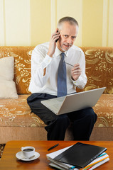 Senior Businessman Working with Computer and Smartphone