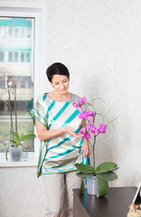 woman with Phalaenopsis orchid indoor