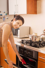 woman gets food from the oven