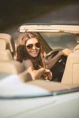 Beautiful young woman witting in a car on driver seat