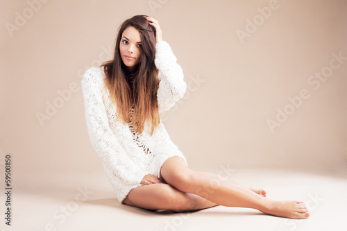 Tender woman in white woolen sweater against beige background