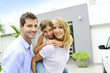 Parents with kid standing in front of new home