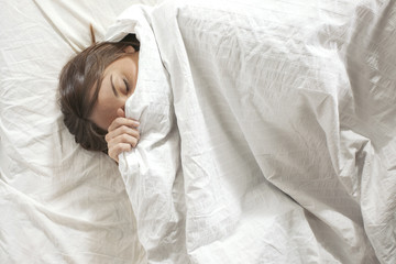 Woman covered with pillow. Sleeping in a white bed.