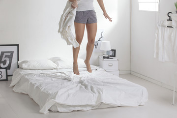 The white bedroom. Woman with a blanket jumping on a bed.