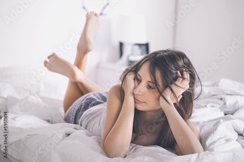 Young woman resting as she lies awake in bed.