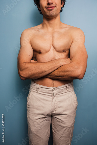 Sexy young man with his arms crossed