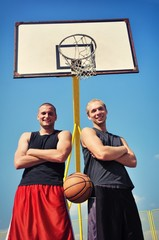 Two basketball players smiling on the court