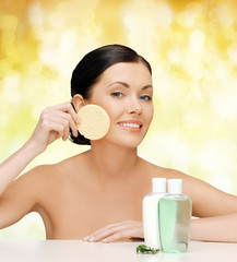 smiling woman with sponge and cosmetic bottles