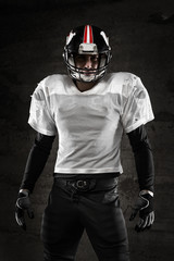 Portrait of american football player looking at camera on dark b