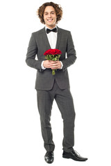 Groom in tuxedo posing with a bouquet