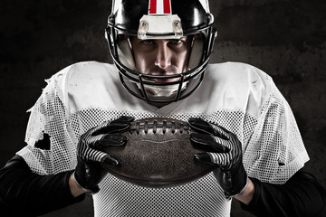 Portrait of american football player holding a ball and looking
