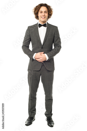 Hansome groom posing with clasped hands