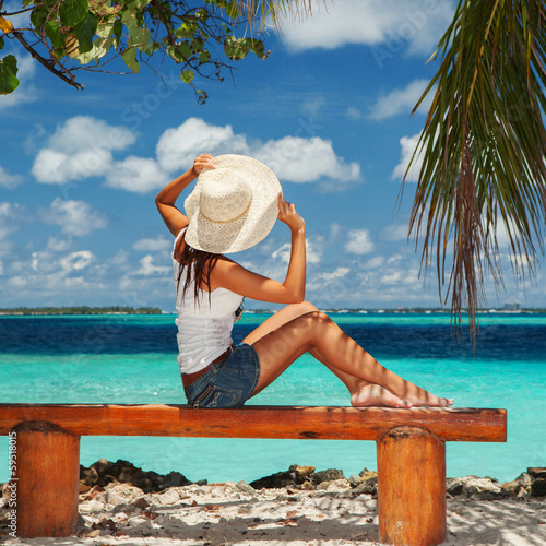 Fashion woman siting on a bench at the beach