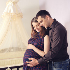 Couple future parents near a cot.