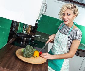 Smiling woman cooking healthy food at home