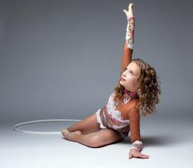 Graceful young gymnast dancing with hoop