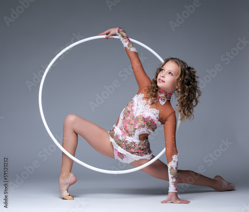 Image of elegant young gymnast dancing with hoop