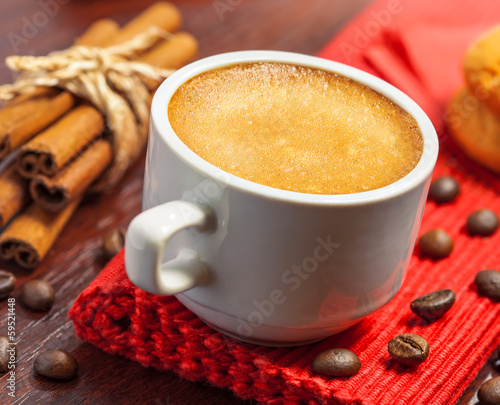 Coffee cup, cookies and cinnamon on a table