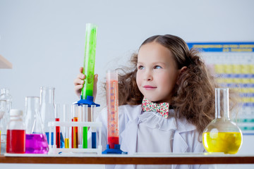 Image of cute girl posing with colorful flasks