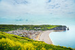 Etretat village, beach and Aval cliff landmark on ocean. Normand