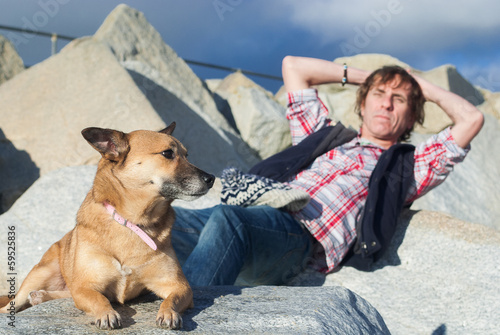 Man relaxing with his dog at the beach