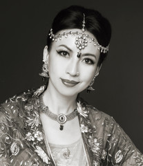 woman in traditional clothing with bridal makeup and jewelry.