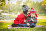 Little Girl Whispers A Secret to Baby Brother Outdoors