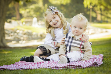 Sweet Little Girl Hugs Her Baby Brother at the Park.