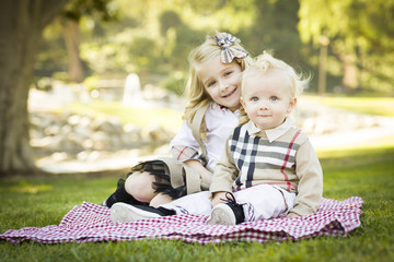 Sweet Little Girl with Her Baby Brother at the Park.