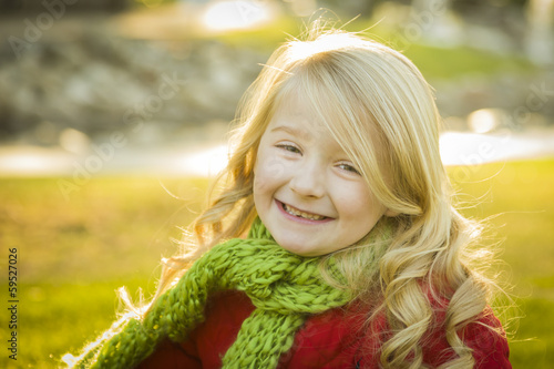 Little Girl Wearing Winter Coat and Scarf at the Park.