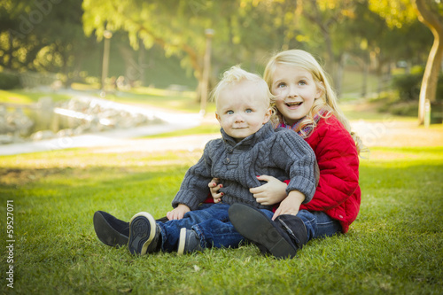 Little Girl with Baby Brother Wearing Coats at the Park.