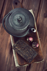Tetsubin teapot and various dry tea, rustic wooden background
