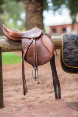 Horse saddle hanging on a wooden stand