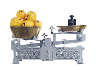 Old-fashioned balance scale with quinces isolated on white