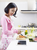 asian housewife looking at tablet computer while cooking