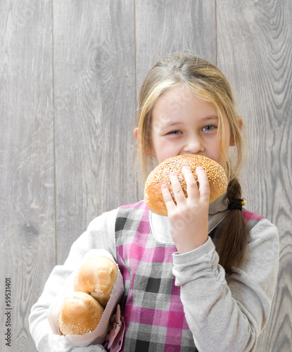 girl  bites a piece of bread